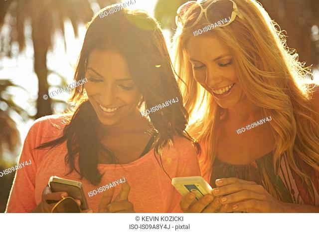 Women sharing text messages on phone
