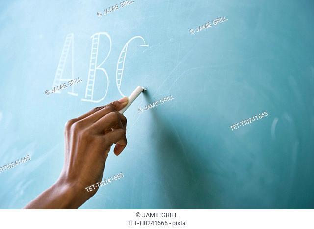 Close up of woman's hand writing alphabet on blackboard
