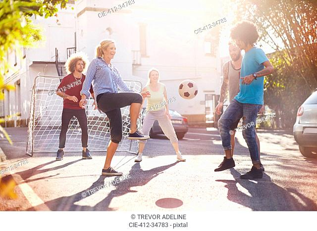 Friends playing soccer in sunny summer street