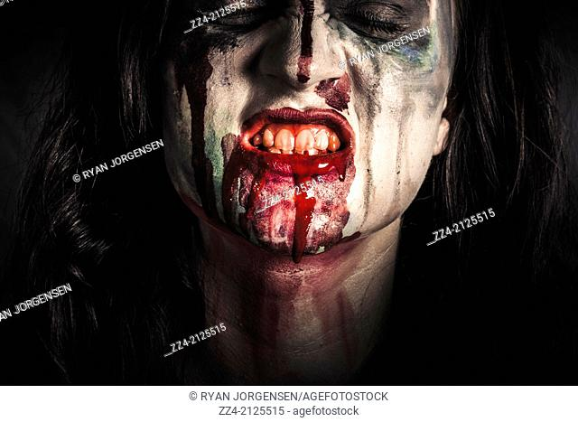 Close photo on the face of dark vampire girl expressing pain with blood mouth