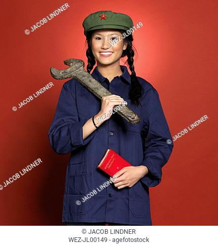 Young chinese woman, holding big spanner and red book