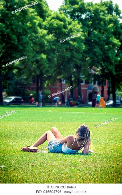 Cute girl relaxing on the grass of VondelPark in Amsterdam