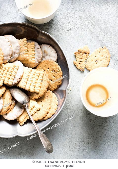 Overhead view of cookies in metal bowl and empty cups