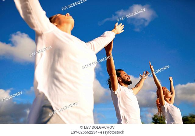 fitness, sport, yoga and healthy lifestyle concept - group of people meditating outdoors