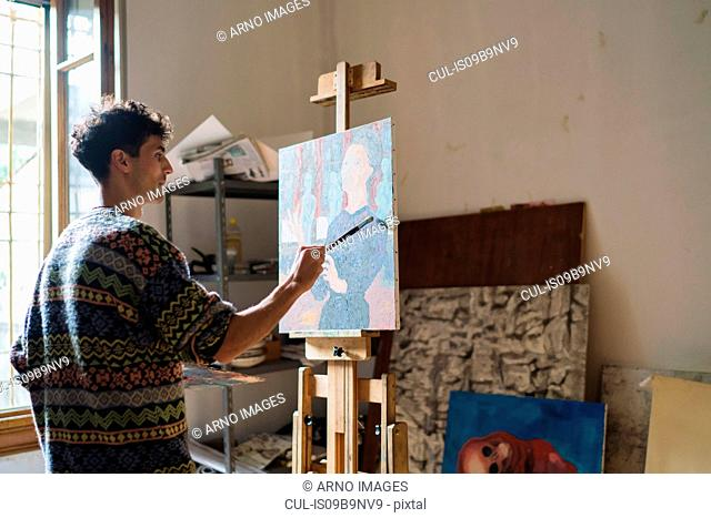 Male artist painting canvas at easel in artists studio
