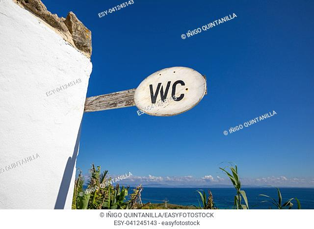 wood signpost with text WC (Water Closet), toilet, in Cadiz, Andalusia, Spain, and on the horizon the ocean and Africa coast