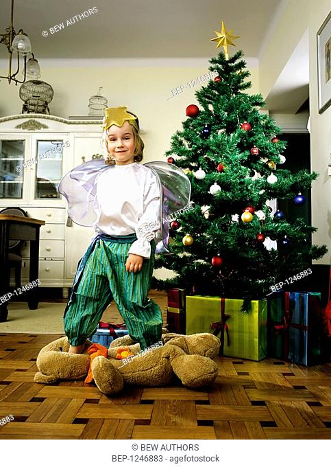 Child boy wearing a fancy dress and standing on a teddy bear at christmas time