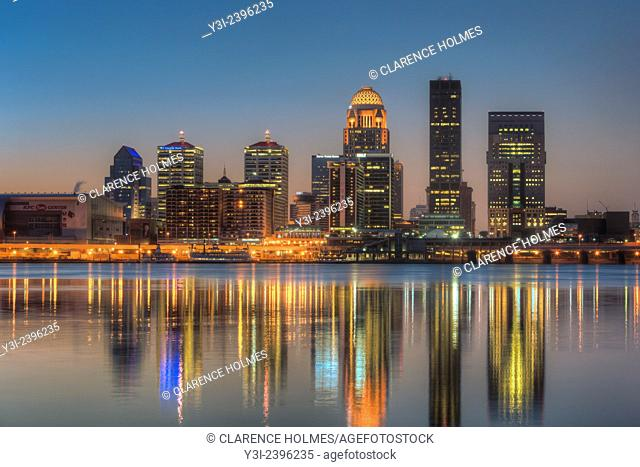 The illuminated skyline of Louisville, Kentucky reflects off the calm surface of the Ohio River under a clear sky during morning twilight shortly before sunrise