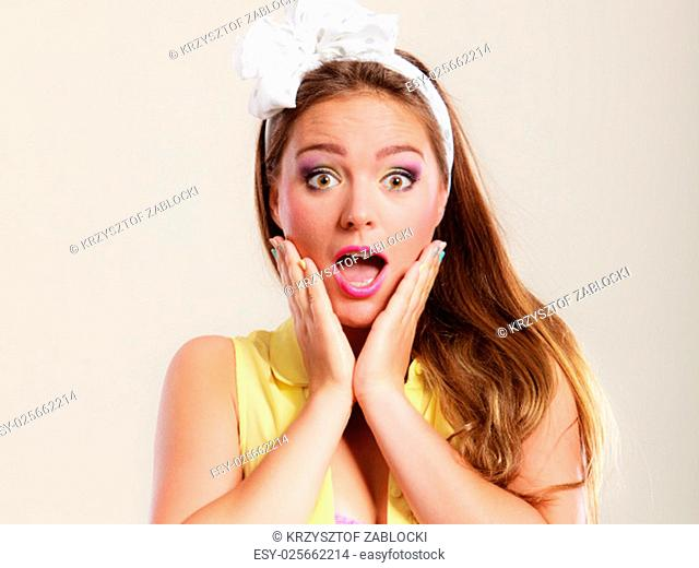 amazed surprised pin up girl with mouth wide open. portrait of astonished young woman with bow