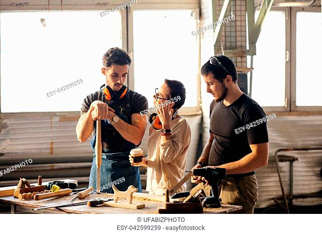 male carpenter showing something to coworker at his notebook papers in workshop