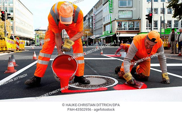 Construction workers apply red paint to a street in Hanover, Germany, 21 October 2013. The colour red marks bicycle lanes there