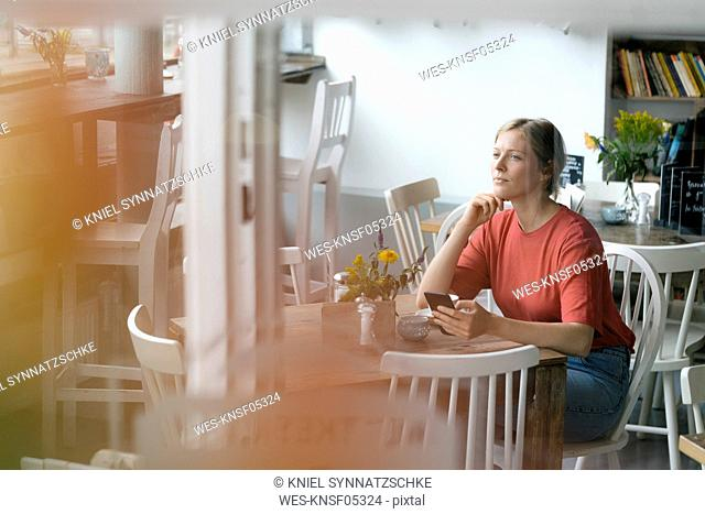 Young woman with cell phone sitting at table in a cafe