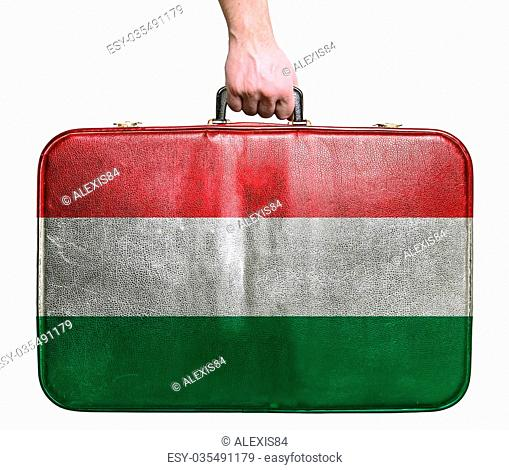 Tourist hand holding vintage leather travel bag with flag of Hungary