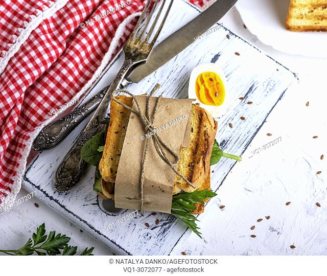 sandwich with vegetables and an egg wrapped in paper on a white board, top view