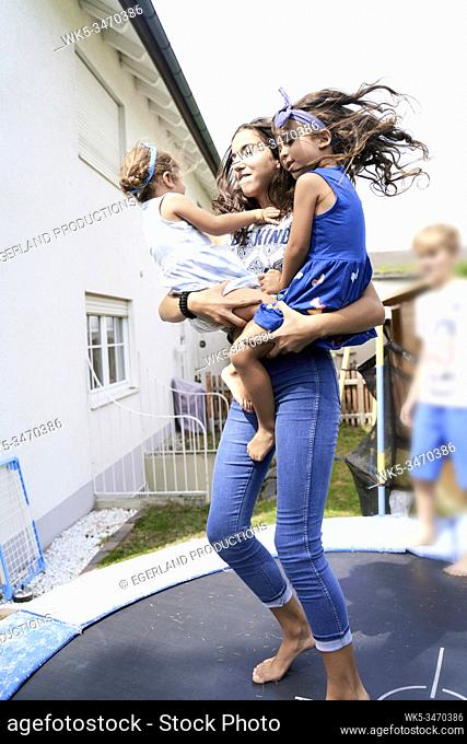 Young girl jumping on trampoline with her little sister in arms