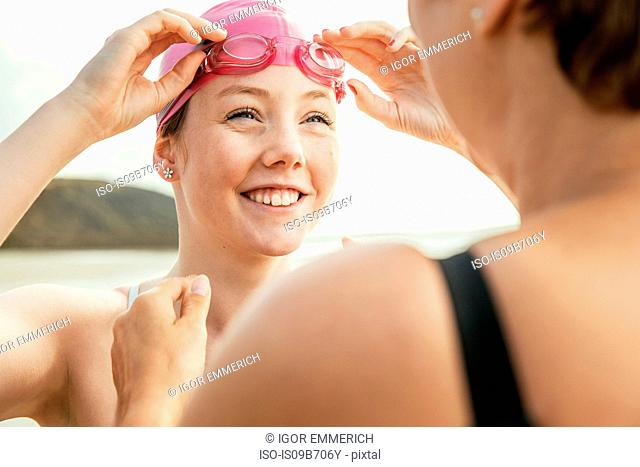 Mother and daughter adjusting swimming goggles on beach, Folkestone, UK