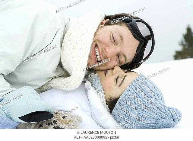 Young couple reclining in snow together, smiling, eyes closed, one on top of the other