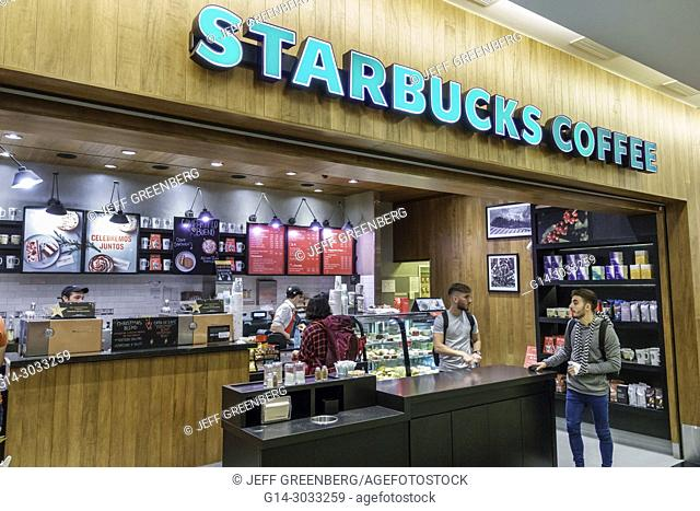 Argentina, Buenos Aires, Ministro Pistarini International Airport Ezeiza EZE, terminal concourse gate area, interior, Starbucks Coffee, counter, man, Hispanic