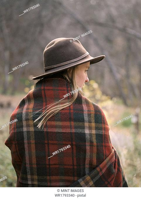 Young blond woman wearing a hat, wrapped in a blanket
