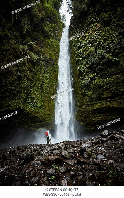 Chile, Patagonia, Osorno Volcano, mother and son standing at Las Cascadas waterfall