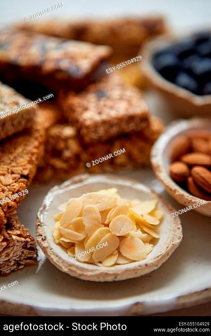 Close up of Almond petals. With various energy nutrition bars in background. Granola bars on ceramic plate over white background