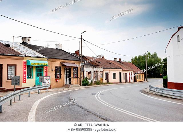 Old houses on curved road in Poland, Odrzywol town, plants grow on sidewalk in home doorframe, architecture view, building exterior in, cloudy day, nobody
