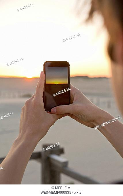 Teenage boy taking picture of sunrise with his smartphone