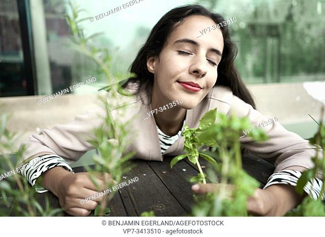 joyful woman smelling fresh thyme and basil plants
