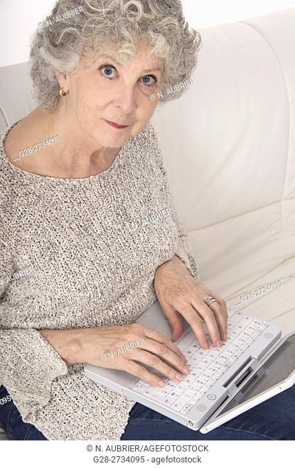 Senior woman sitting on her sofa, Typing on the keyboard of her laptop computer