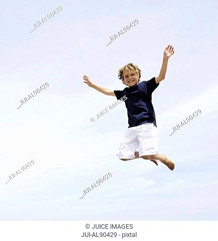 Low angle view of boy jumping