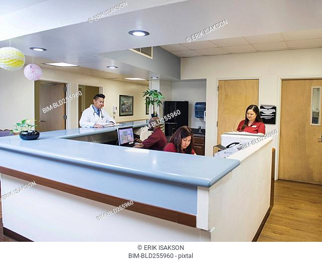 Doctor and nurses at counter in hospital