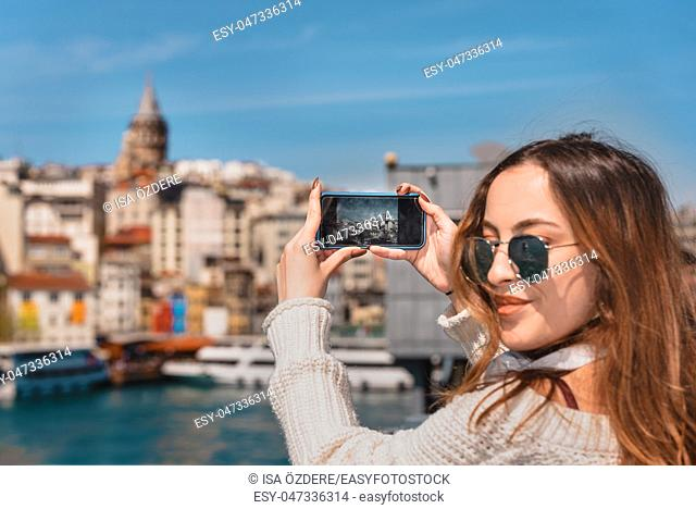 Portrait of beautiful attractive young girl with headphones, smartphone and sunglasses takes selfie on Galata Bridge with view of Suleymaniye Mosque in Istanbul