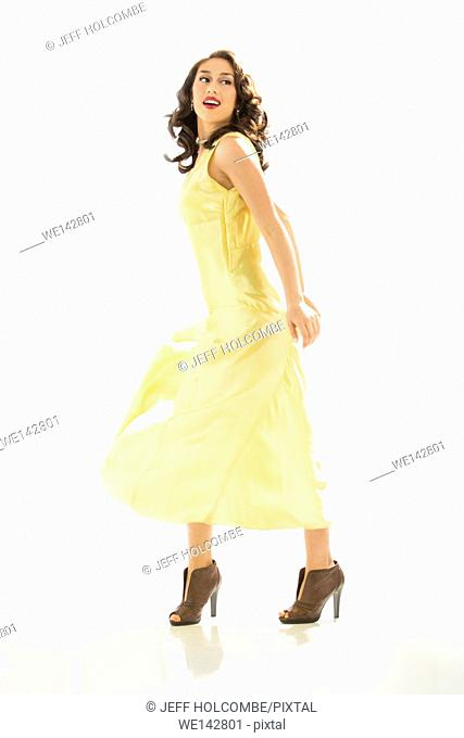 Beautiful young woman happy in vintage yellow dress, full length in brown heels, arms back