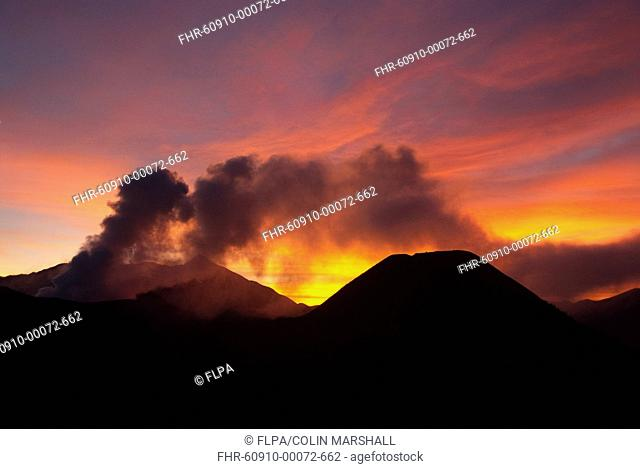 Smoke rising from volcano at sunset, Mount Bromo left and Mount Batok right, Bromo Tengger Semeru N P , East Java, Indonesia