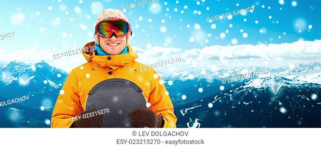 winter, leisure, sport and people concept - happy young man in ski goggles over snowy mountain background