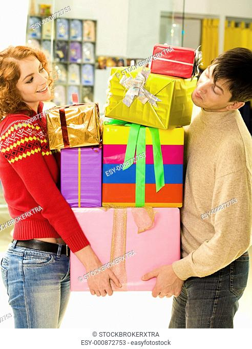 Husband and wife standing with pile of boxes after doing great shopping