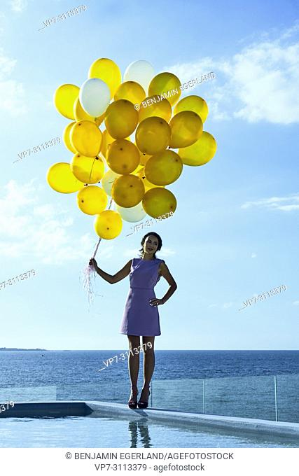 woman holding balloons, standing at pool next to sea. Holiday