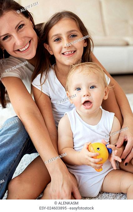 Portrait of a mother with her baby and pre-teen children having fun on white carpet in living room at house