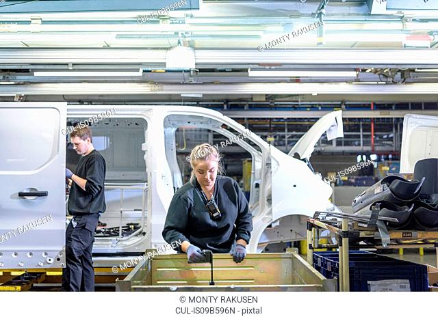 Female apprentice engineer on production line in car factory