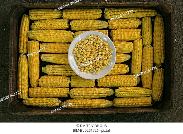 Kernels of corn in bowl on box of corn on cob