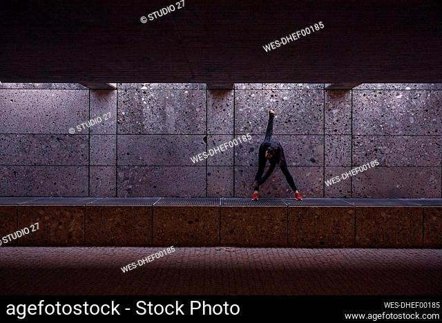 Female athlete warming up before running in pedestrian underpass