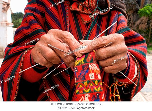 An artisan weaves a hat on the streets of Chinchero in the Sacred Valley near Cuzco. Chinchero is a small Andean Indian village located high up on the windswept...
