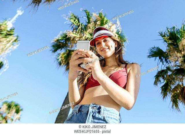 Young woman with sun visor and bikini using cell phone