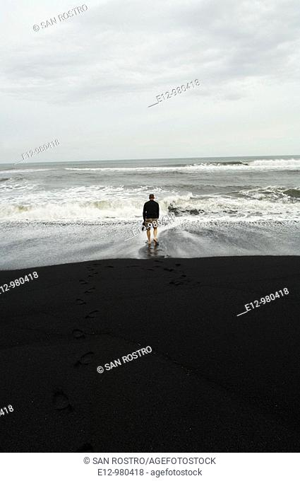 Iceland, Vik village, church, man with feet in the sea at the black sand beach