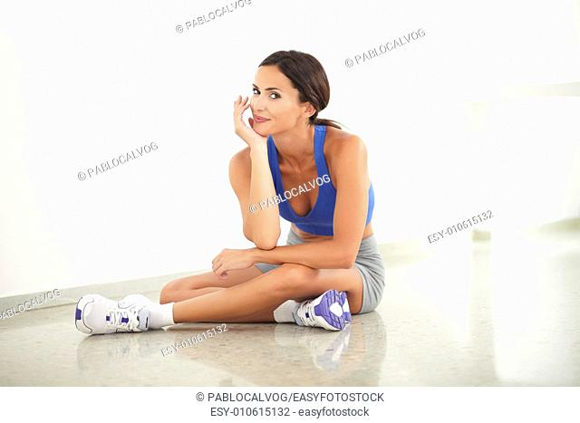 Pretty young female in training clothes sitting in yoga class while looking at you at gym