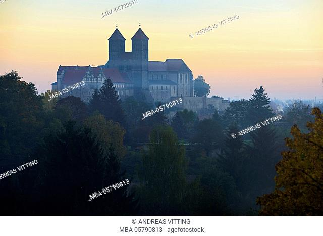Castle hill with collegiate church St. Servatius with red sky and fog patches, UNESCO world heritage, near Quedlinburg, Saxony-Anhalt, Germany