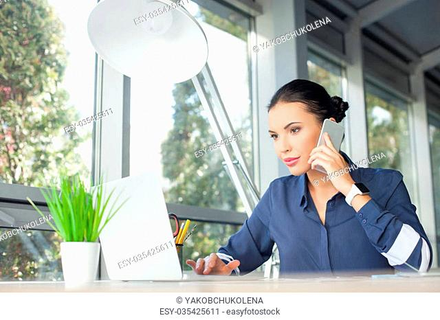Attractive young freelancer is typing on the laptop in her office. She is talking on the mobile phone. The woman is sitting at the table and gently smiling