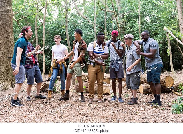 Mens group talking, hiking in woods