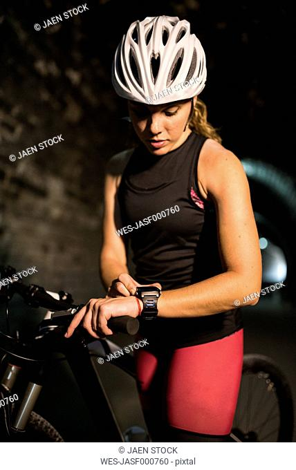 Sportive woman with bicycle looking at smartwatch in a tunnel