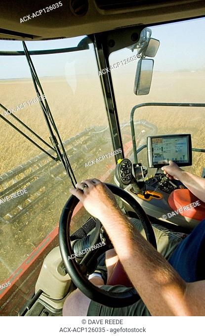 a farmer checks his combine monitor to evaluate crop data during the soybean harvest near Dugald, Manitoba, Canada